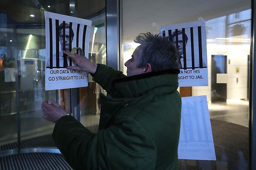 A man putting up posters depicting now suspended Cambridge Analytica CEO Alexander Nix behind bars, at the entrance of the company's offices in central London on Tuesday.