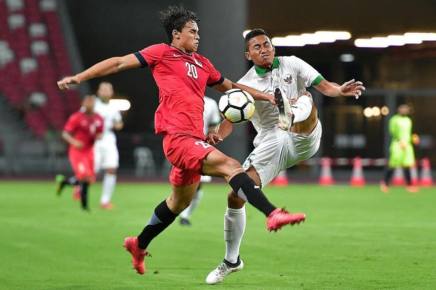 Singapore's Ikhsan Fandi squaring off with Indonesia's Ricky Fajrin Saputra at the National Stadium last night. The Young Lions need to improve in numerous areas if they are to get the nod for August's Asiad in Indonesia.