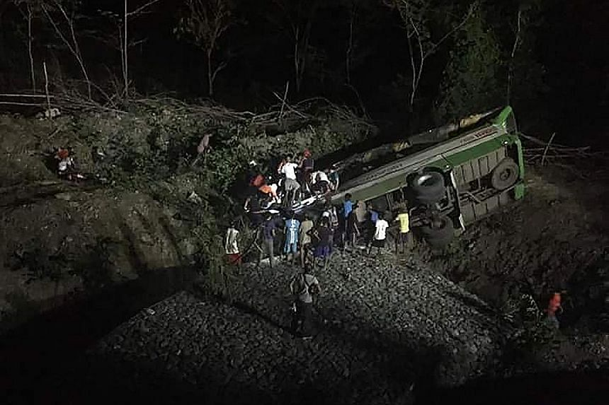 Rescue workers searching for survivors in the passenger bus, which veered off a road and plunged into a ravine near Sablayan town, about 195km south of Manila, yesterday. The bus company involved in the crash has been suspended.