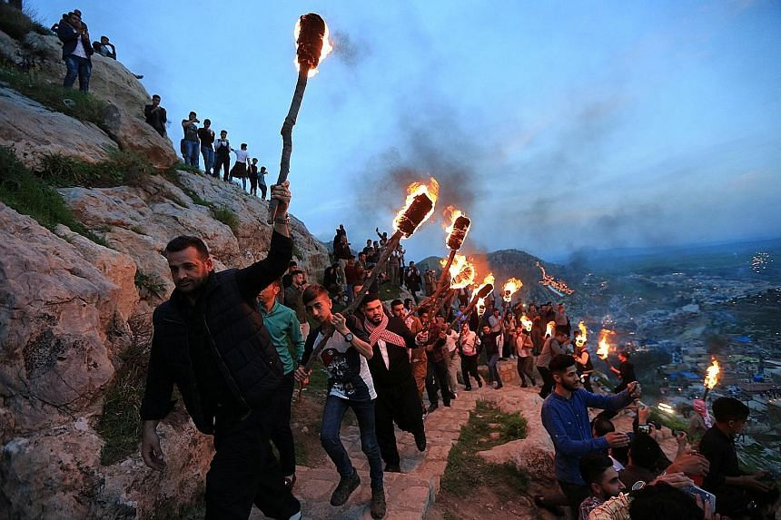 Iraqi Kurdish people carrying torches up a mountain in the Iraqi town of Akra on Tuesday, in celebration of Newroz Day. The festival, held on the spring equinox, marks the arrival of spring and the new year. It is considered the most important festiv
