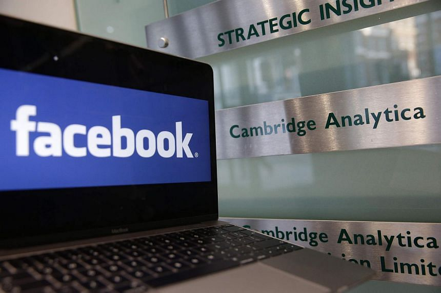 A laptop showing the Facebook logo is held alongside a Cambridge Analytica sign at the entrance to the building housing the offices of Cambridge Analytica in central London on March 21, 2018.