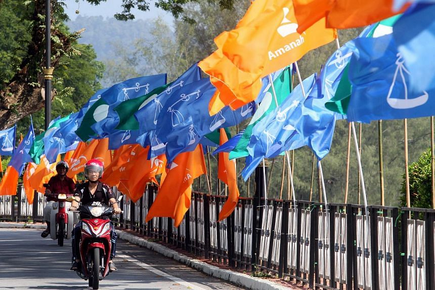 A motorcyclist riding past the flags of the National Trust Party (Amanah), Barisan Nasional and the All-Malaysia Islamic Party.