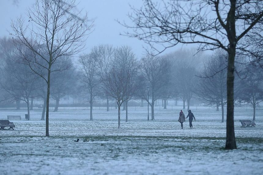 Walkers cross a snow-covered Clapham Common in London on March 18, 2018.