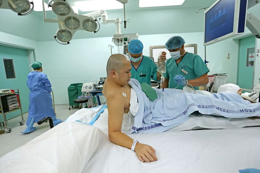 Associate Professor See asking Mr Oh to raise his right arm to test his movement. Awake brain surgery is done in less than 10 per cent of brain tumour cases at the institute, when surgeons need to operate on an area of the brain that involves or is c