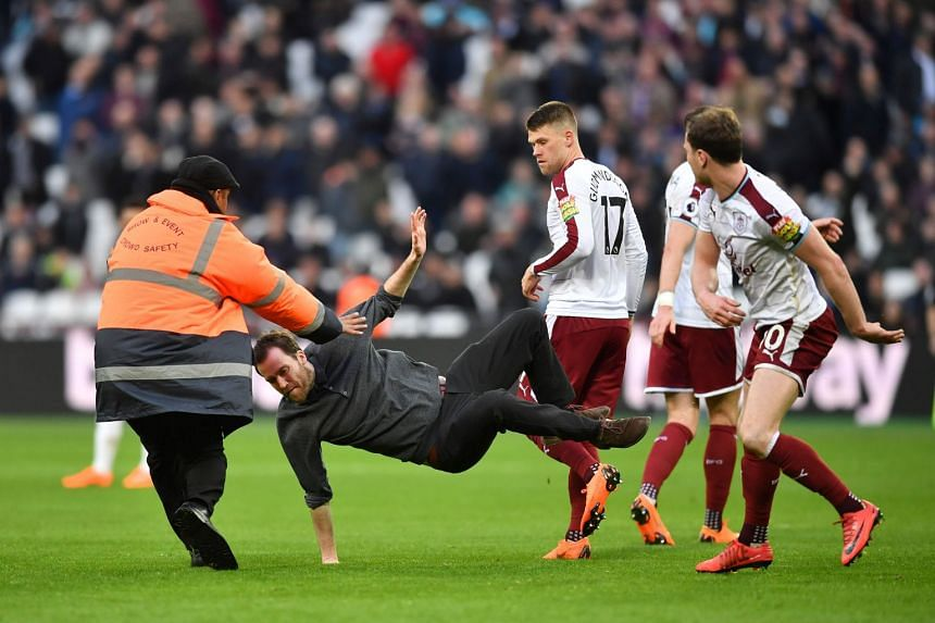 Burnley striker Ashley Barnes trips up a pitch invader during the English Premier League football match against West Ham United at The London Stadium on March 10, 2018.