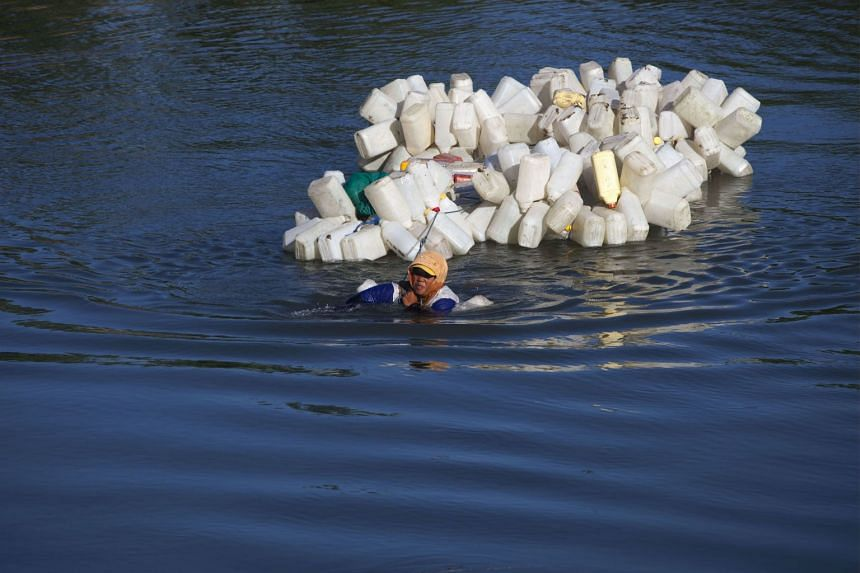 Indonesian villager Mama Hasria swimming with hundreds of jars tied to her back to get clean water in Tinambung, West Sulawesi, on March 22, 2018.