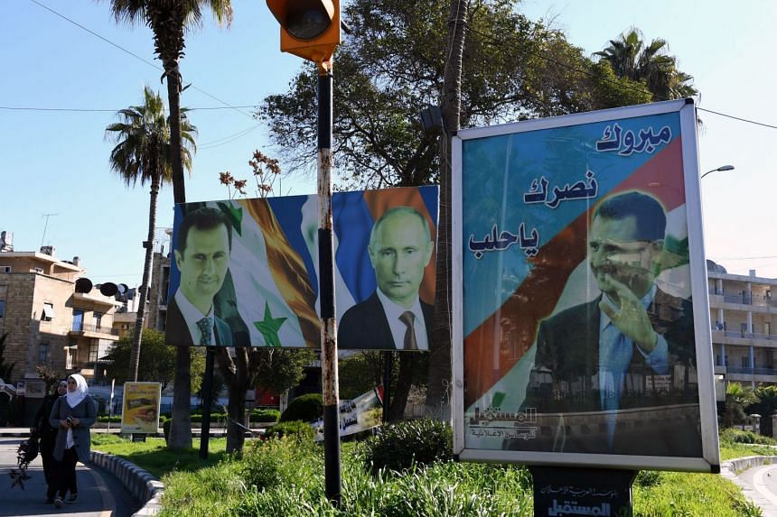 Portraits of Russian President Vladimir Putin, Syrian President Bashar al-Assad and Lebanese Hezbollah Leader Hassan Nasrallah hang outside a jewellery shop Aleppo on March 17, 2018.