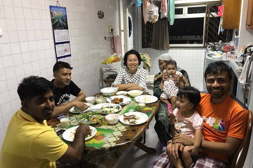 Mr Mohamad Farid (in orange) with his family and two foreign workers at his parents' flat in Bedok in December 2017.