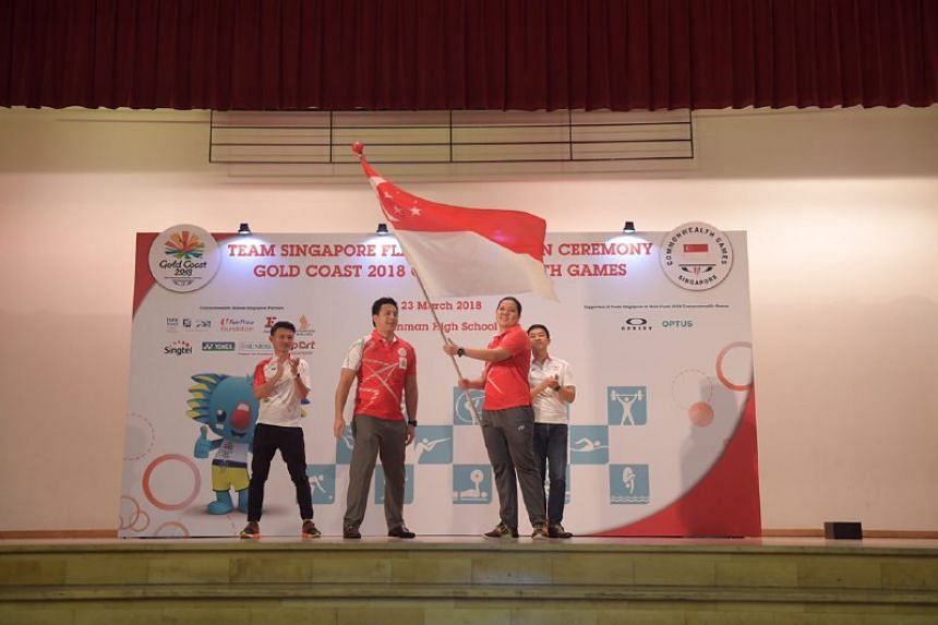 Mark Chay, chef de mission of the Gold Coast 2018 Commonwealth Games, hands the Singapore flag to shooter Teo Shun Xie, at Dunman High School, on March 23, 2018.