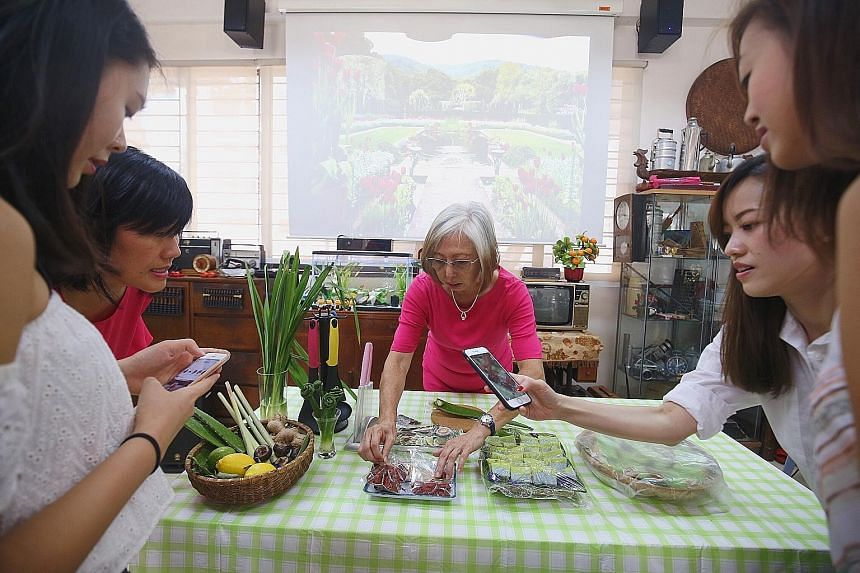 Madam Maria Yee sharing how she uses herbs and plants she grows in her cooking at the Touch Seniors Activity Centre in Geylang Bahru. She says the Airbnb tie-up gives her a chance to share her love for gardening.