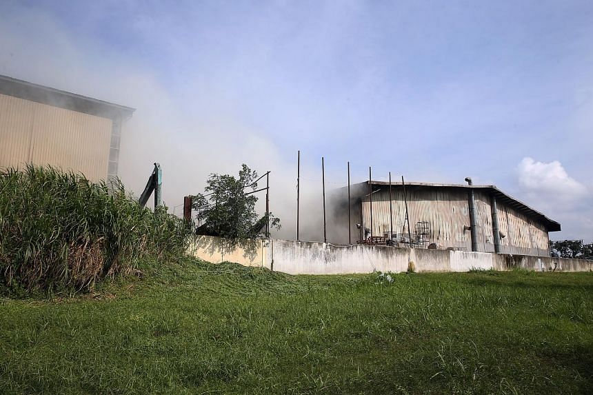 """SCDF said the fire had involved waste materials contained inside the building, which are """"typically deep seated and difficult to be extinguished quickly"""". Thick smoke surrounding the warehouse in Kranji Crescent. The facility is operated by waste man"""