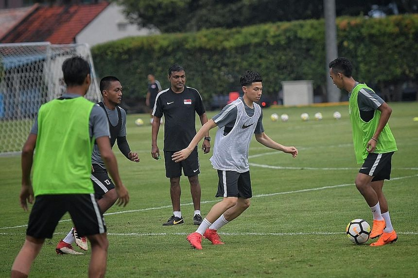Ben Davis of Fulham Under-18s, who earned his first national team call-up, closing down PKNS player Faris Ramli in training as coach V. Sundram Moorthy observes. There are 10 overseas-based players in the squad.