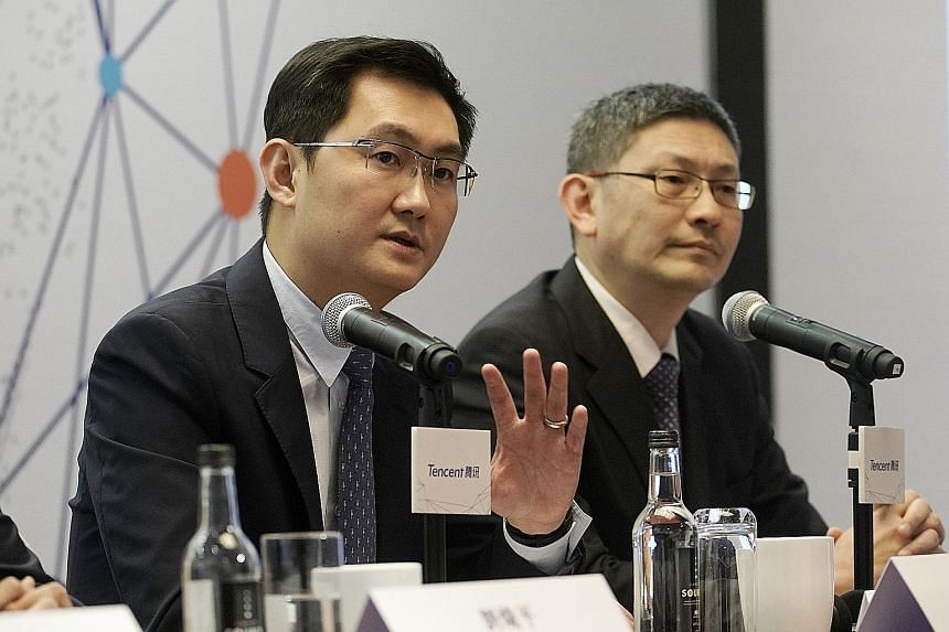 Mr Ma Huateng (left), chairman and chief executive officer of Tencent, with chief financial officer John Lo at a news conference in Hong Kong on Wednesday. The firm plans to keep spending on areas from artificial intelligence to video, in a bid to an