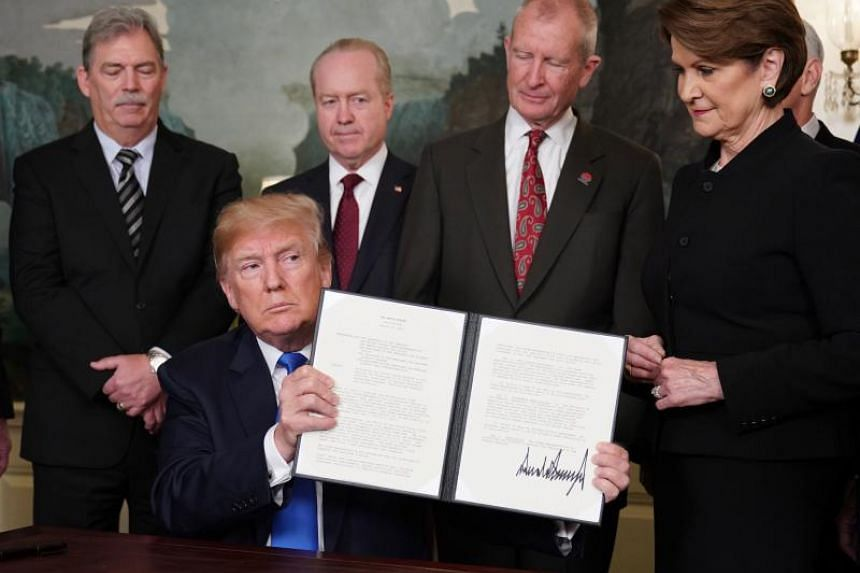 US President Donald Trump signs trade sanctions against China in the Diplomatic Reception Room of the White House in Washington, DC, on March 22, 2018.