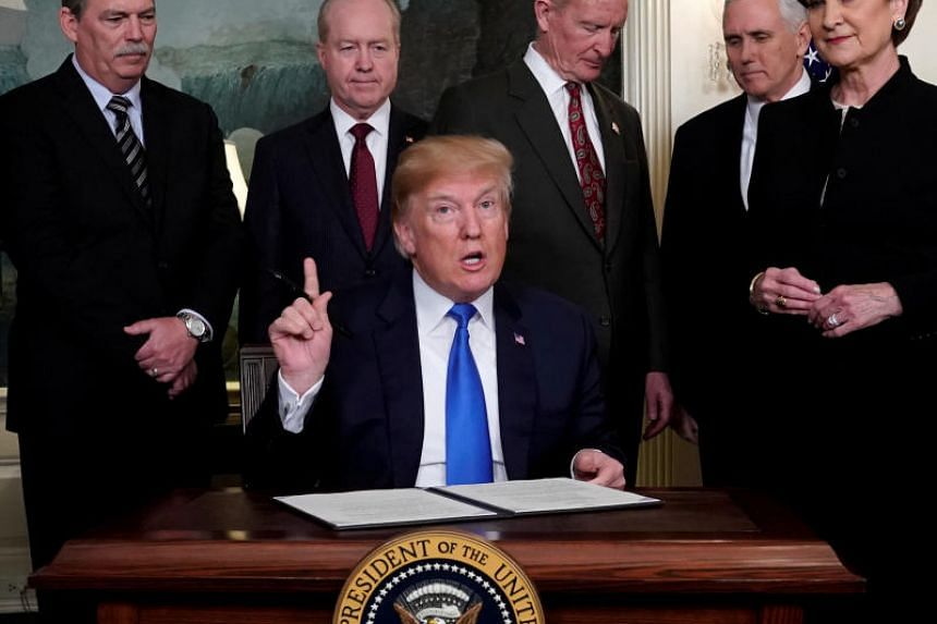 US President Donald Trump, surrounded by business leaders and administration officials, prepares to sign a memorandum on intellectual property tariffs on high-tech goods from China, at the White House in Washington, US on March 22, 2018.
