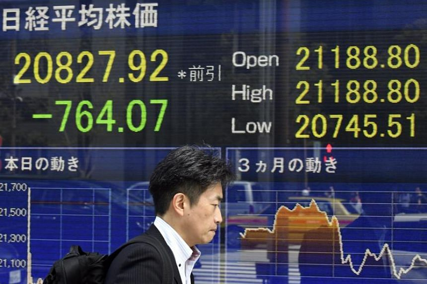 A pedestrian walks past a stock market indicator board in Tokyo, Japan, on March 23, 2018.