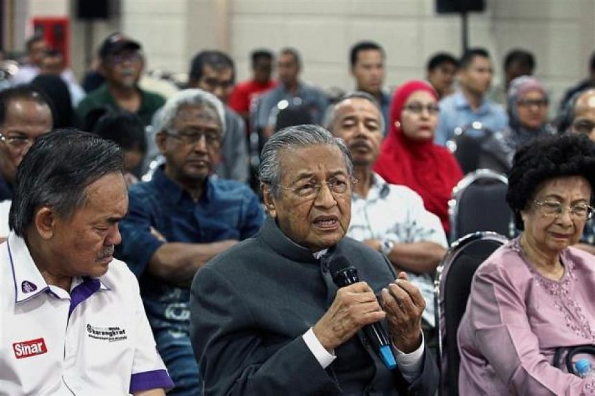 Dr Mahathir Mohamad (centre), accompanied by Dr Siti Hasmah (right), speaking at the forum in Shah Alam, on March 22, 2018.