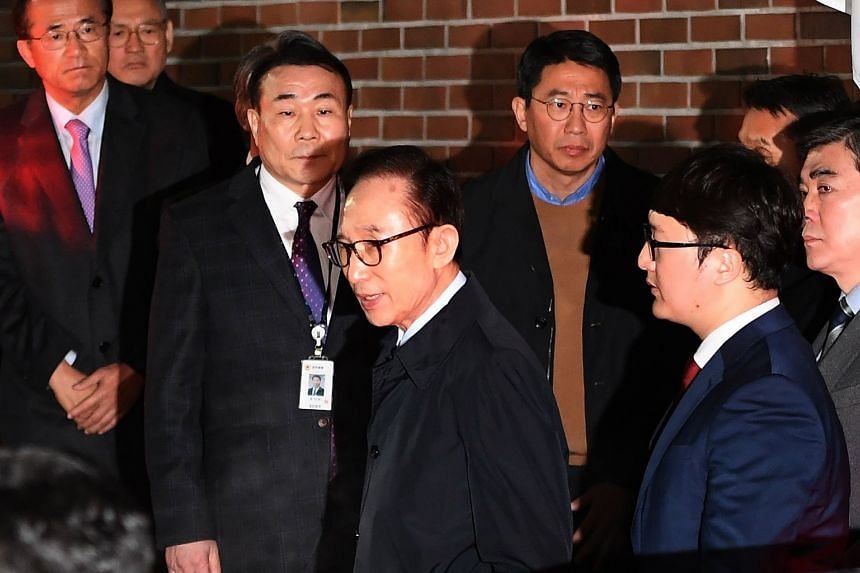 Former South Korean president Lee Myung Bak (centre) leaving his home to be transferred to a detention centre in Seoul, on early March 23, 2018.