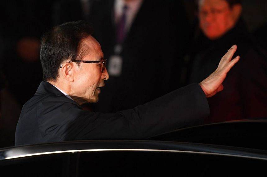 Former South Korean president Lee Myung Bak gestures as he gets into a car to be transferred to a detention centre in Seoul, on early March 23, 2018.