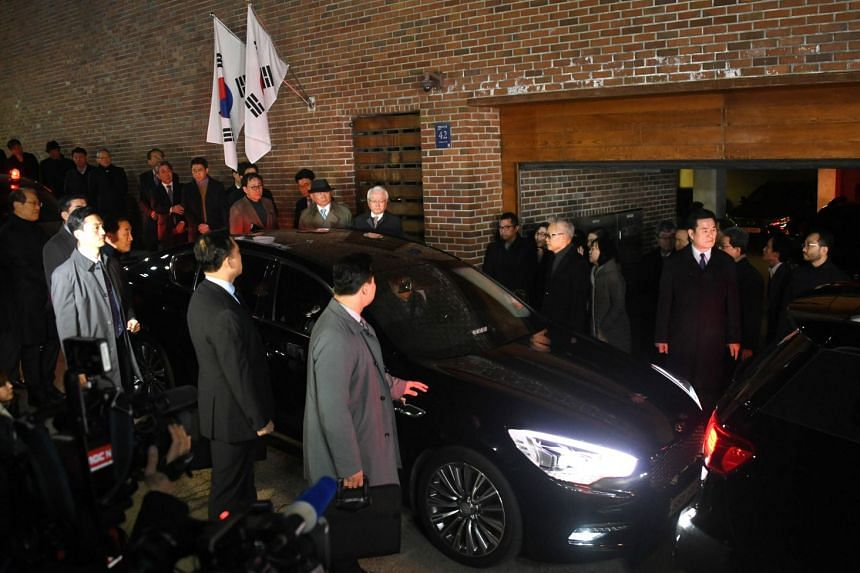 A car carrying former South Korean president Lee Myung Bak is seen outside his home as he is transferred to a detention centre, on early March 23, 2018.