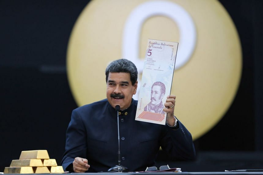 Venezuelan President Nicolas Maduro holds an enlarged image of the new five Venezuelan Bolivar note during a press conference in Caracas, on March 22, 2018.