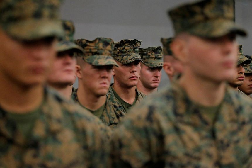 US Marines stand in formation during a ceremony marking the start of Talisman Saber 2017, a biennial joint military exercise between the United States and Australia, aboard the USS Bonhomme Richard amphibious assault ship, on June 29, 2017.