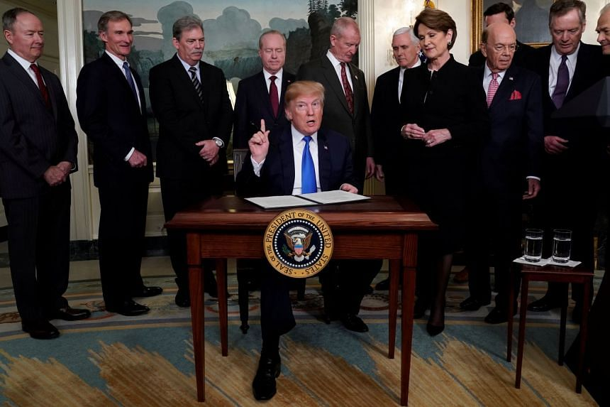US President Donald Trump, surrounded by business leaders and administration officials, prepares to sign a memorandum on intellectual property tariffs on high-tech goods from China, on March 22, 2018.