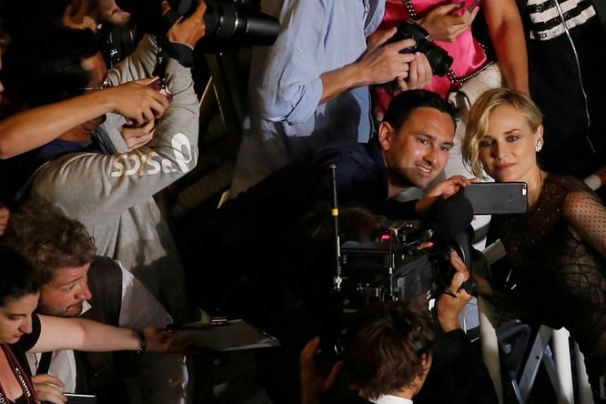 A cinema fan takes a selfie with cast member Diane Kruger at the 70th Cannes Film Festival.