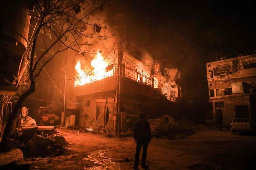 Flames erupting in a building following regime bombardment in Douma, one of the few remaining rebel-held pockets in Eastern Ghouta, on March 23, 2018.