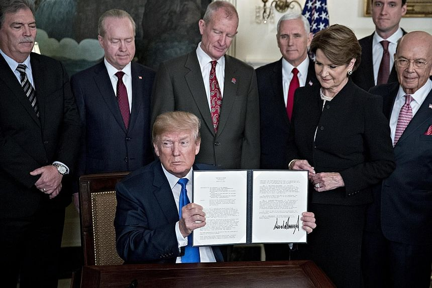 US President Donald Trump holding a signed presidential memorandum on US tariffs on Chinese imports, surrounded by business leaders and members of his administration, in the White House on Thursday. A trade war between the two economic giants will no