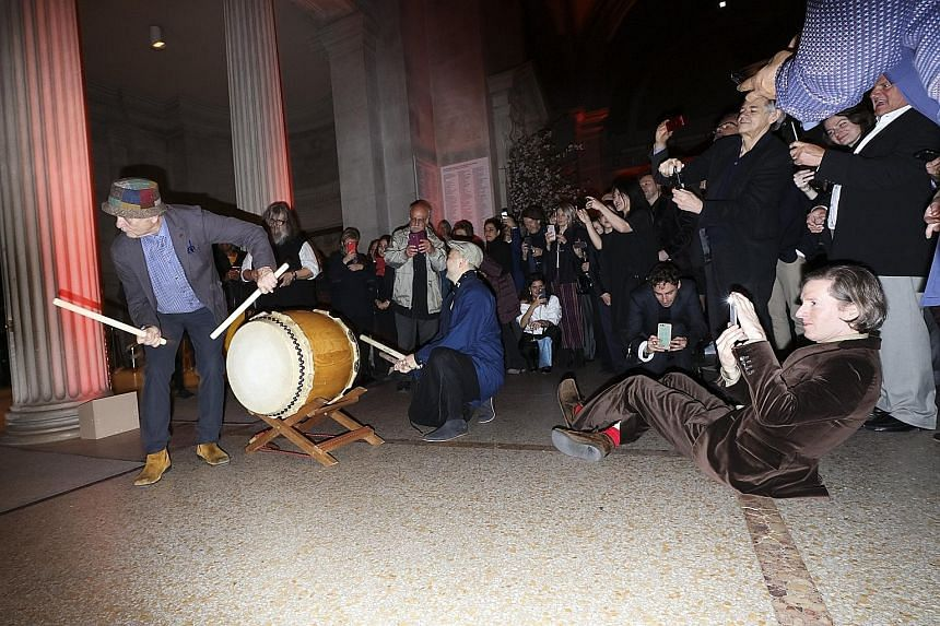 Director Wes Anderson plays photographer as actor Bill Murray hits the taiko drums at the reception for the New York premiere of Anderson's film, Isle Of Dogs, at the Metropolitan Museum of Art in New York on Tuesday.