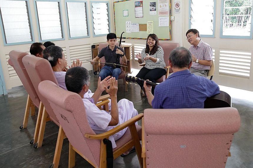 Social work co-ordinator Regina Mary, 48, with volunteers (from far left) Ryan Teo, 21, Chris Koh, 65, and Chio Cheng Kay, 76, (back to camera, with guitar) enjoying a singing session with TB patients.