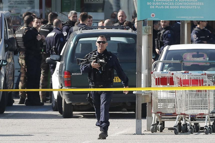 Armed officers in the parking lot of the supermarket in France where a gunman claiming allegiance to ISIS had taken hostages. He was later killed by police.