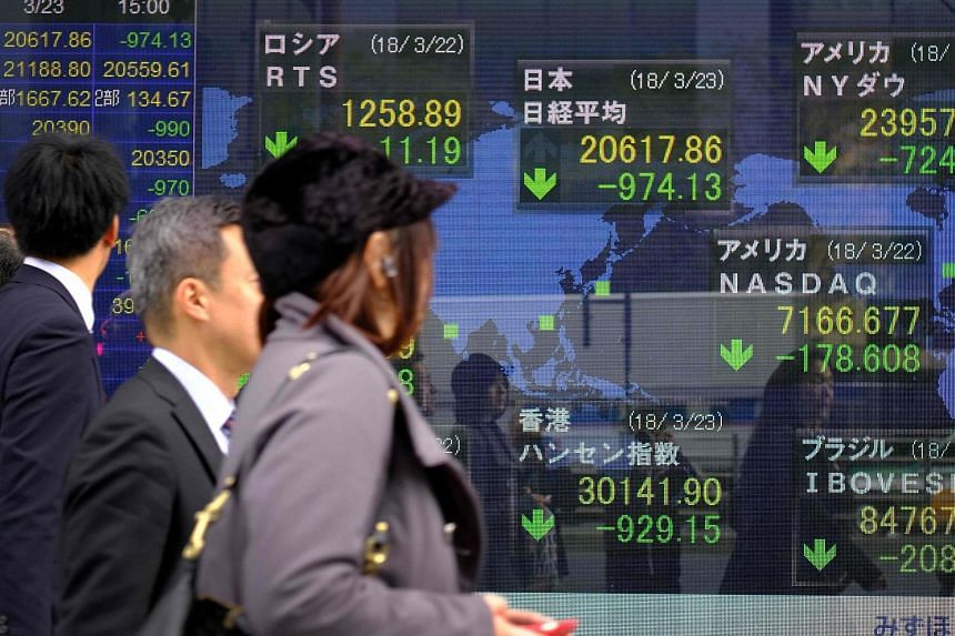 An electronic board showing losses on Japan's Tokyo Stock Exchange yesterday. Investors across Asia braced themselves for a potential trade war after China unveiled countermeasures against the US.