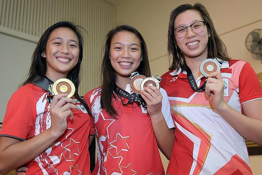 (From left) Fong Kay Yian and Ashlee Tan (diving) and Chantal Liew (open water swimming) were presented with their upgraded medals.
