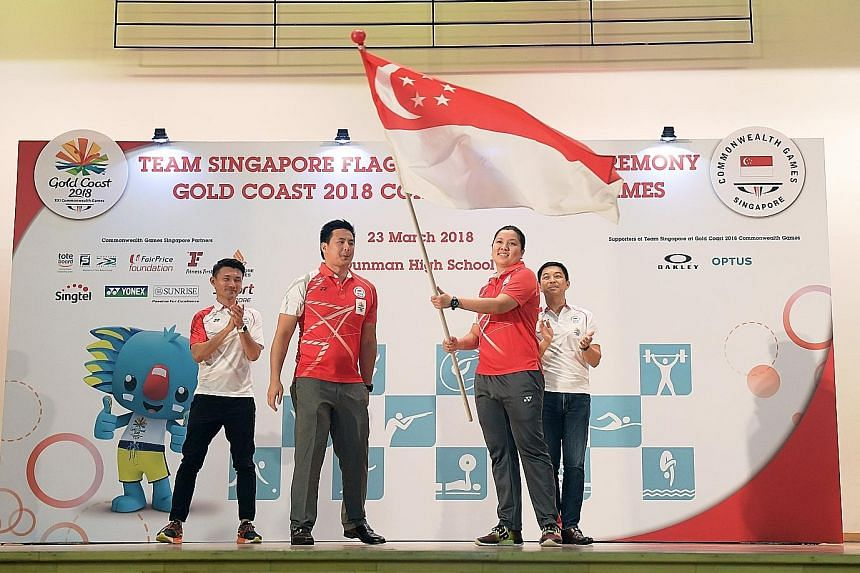 Former swimmer Mark Chay, chef de mission for the Commonwealth Games, handing the Singapore flag to shooter Teo Shun Xie at a ceremony at Dunman High School yesterday. Observing are Parliamentary Secretary for Culture, Community and Youth Baey Yam Keng (l