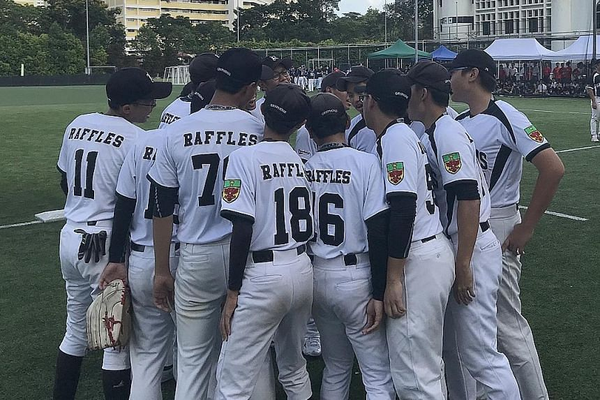 Raffles Institution's softball players, seen here in a team huddle yesterday, beat defending champions Catholic High School 6-4 in the B Division boys' final on home turf.