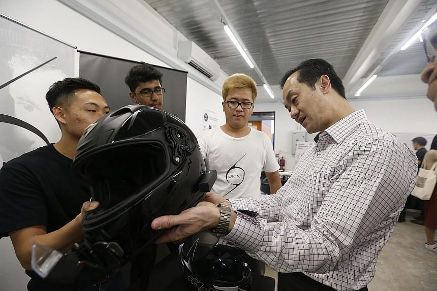 Dr Koh Poh Koon looking at an OMNi-smart helmet, which is made by OMNI-, a start-up firm supported by the Robotics Centre. It is fitted with information display, GPS navigation, dual-view camera and in-built speakers, and can be controlled by a mobil