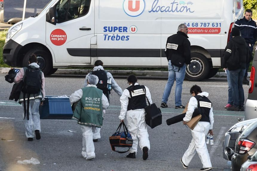 French forensic officers carry away material after a man took hostages at the Super U supermarket in the town of Trebes, southern France on March 23, 2018.