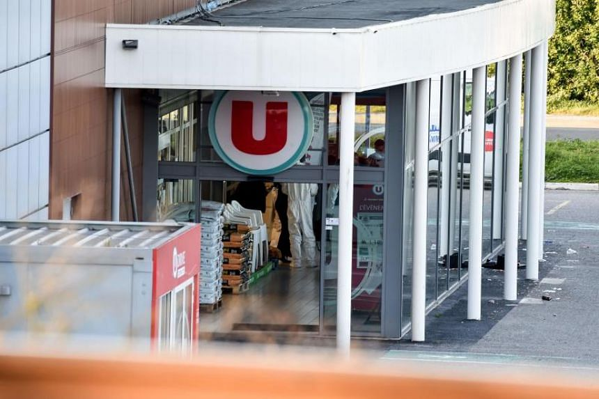 French security and forensic officers are seen inside the Super U supermarket in the town of Trebes, southern France, where a man took hostages killing three before he was killed by security forces on March 23, 2018.