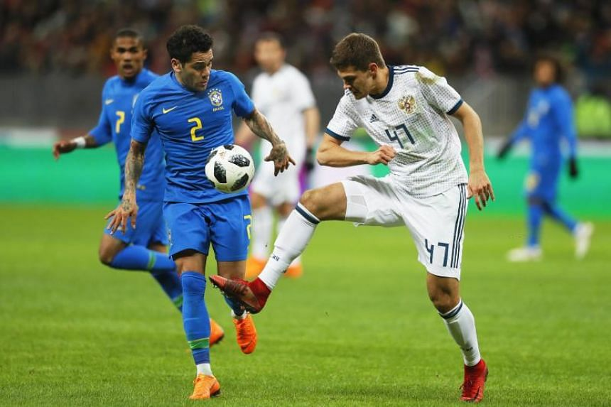 Russia's Roman Zobnin (right) in action against Brazil's Dani Alves during the International Friendly soccer match between Russia and Brazil at Luzhniki stadium in Moscow, Russia, on March 23, 2018.