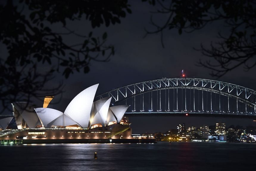 Sydney Harbour Bridge and the Opera House are seen before being plunged into darkness for the Earth Hour environmental campaign on March 24, 2018.