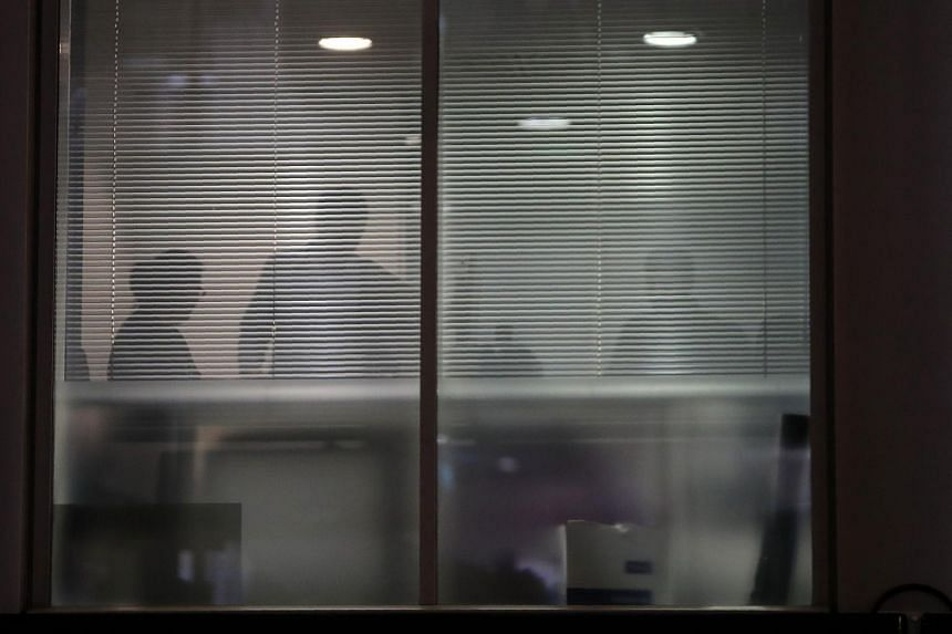 The silhouettes of people are seen through blinds inside the offices of Cambridge Analytica in central London on the evening of March 23, 2018, just hours after a judge approved a search warrant of the offices.
