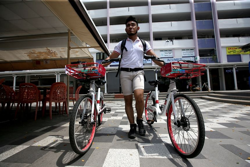 SG Bike operation supervisor Syed Al-Syahab bringing two SG Bikes which was found parked in the middle of a walkway, to an approved parking spot.