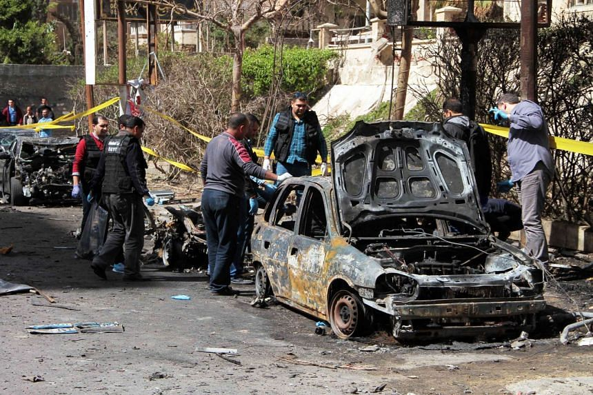 Egyptian forensics check a destroyed vehicle at the site of a bomb attack, which hit a convoy of the city's security chief, in Alexandria on March 24, 2018.