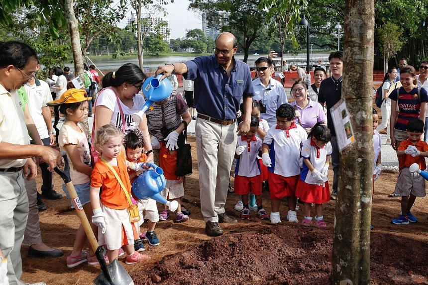 Deputy Prime Minister Tharman Shanmugaratnam playfully dousing water on children during a tree-planting activity at Jurong Lake Gardens West on March 24, 2018.