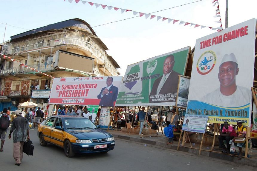 Electoral posters of Sierra Leone's two presidential candidates, Julius Maada Bio (centre) and Samura Kamara (right) are seen in central Freetown on March 12, 2018.