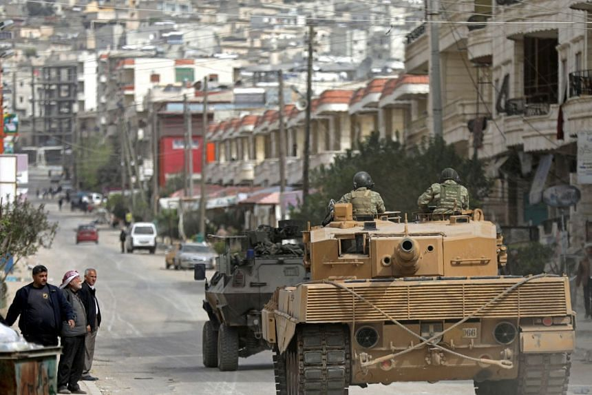 Turkish forces patrol an area in Afrin, Syria on March 22, 2018.