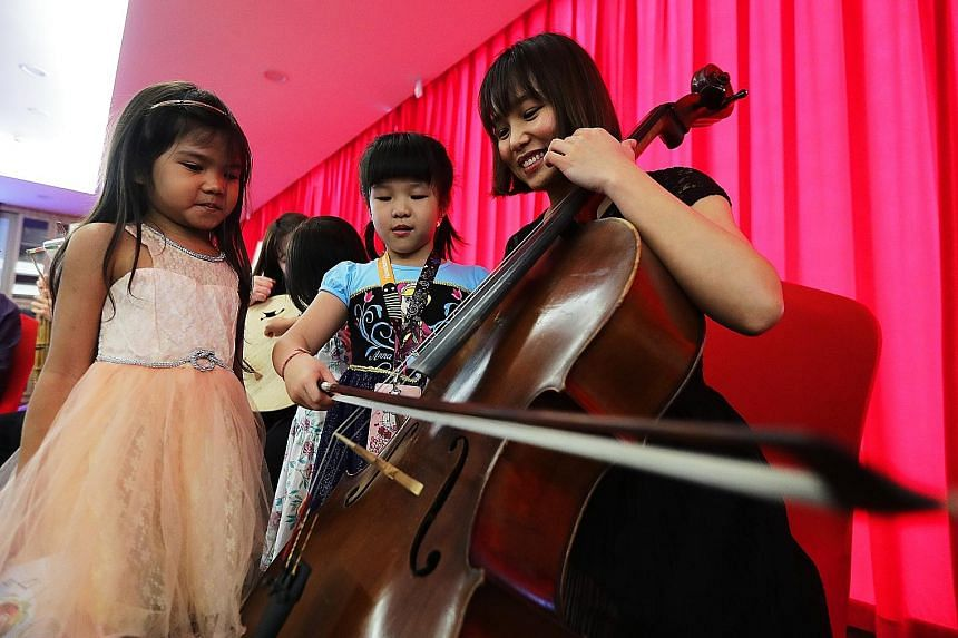 Professional musician Terresa Huang, 28, giving pointers on how to play the cello. For many of the children, it was their first time seeing such instruments. Professional musician Kevin Cheng, 28, playing the sheng at the Red Bean Concert yesterday.