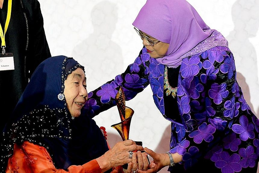 """Puan Noor Aishah, 84, the wife of Singapore's first president Yusof Ishak, receiving a trophy from President Halimah Yacob. She was commended for """"breathing new life"""" into the Istana and for her quiet determination, humility and charm."""
